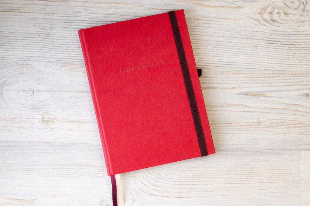 Красный ежедневник с списком контактов и планингами